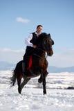 Cheval d'équitation de jeune homme extérieur en hiver Image stock