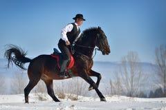 Cheval d'équitation de jeune homme extérieur en hiver photos stock