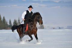 Cheval d'équitation de jeune homme extérieur en hiver Photographie stock libre de droits