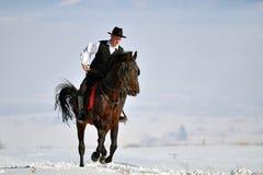 Cheval d'équitation de jeune homme extérieur en hiver Images stock