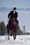 Cheval d'équitation de jeune homme extérieur en hiver photo stock