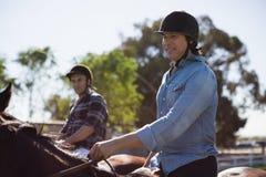 Cheval d'équitation masculin de deux amis dans le ranch Photo libre de droits