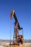 Cheval de basculage de Rusty Oilfield Pumpjack au-dessus d'une tête de puits B clair photo libre de droits
