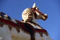 Cheval de carrousel en parc d'attractions sur un ciel bleu Images libres de droits
