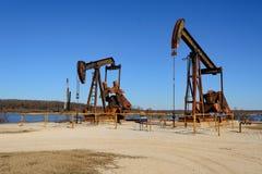 Cheval de deux Rusty Oilfield Pumpjacksrocking au-dessus d'une tête de puits Cle image libre de droits