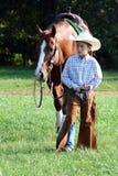 Cheval de marche de jeune cowboy Photographie stock libre de droits