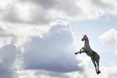 Cheval et nuages de jouet Images stock