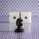 Cheval noir d'échecs à l'arrière-plan d'une matrice pour jouer des dominos images libres de droits