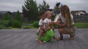 Cheval sautant de jouet de vert d'équitation d'enfant de fils de bébé garçon dans un jardin vert - scène chaude d'été de couleur  banque de vidéos