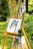 Chevalet avec la toile dans un jardin Photos libres de droits