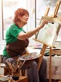 Chevalet de peinture d'artiste dans le studio Femme supérieure authentique images stock