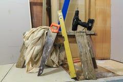 Chevalet de sciage du ` s de charpentier avec des outils : Scie, niveau d'esprit, nappe protectrice et foret électrique images stock