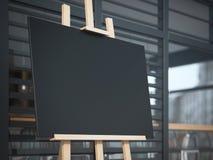 Chevalet en bois avec une toile sur la rue près du café Image libre de droits