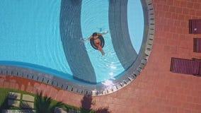 Chevalets par la piscine et la femme d'hôtel dans l'eau sur l'anneau banque de vidéos