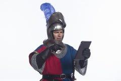 Chevalier à l'aide du comprimé électronique horizontal Photographie stock libre de droits