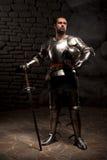 Chevalier médiéval posant avec l'épée dans une pierre foncée Photos stock