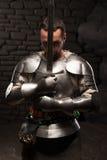 Chevalier médiéval se mettant à genoux avec l'épée Image stock