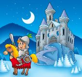 Chevalier sur le cheval avec le château de l'hiver Photographie stock libre de droits