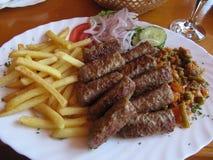 Chevapchichi с картофелем фри и салатом и овощами на белой плите стоковые изображения