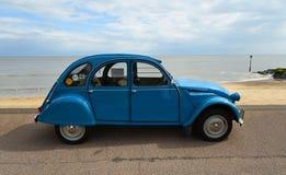 Chevaux azul clásico del deux de Citroen 2CV parqueado en la 'promenade' de la orilla del mar imagen de archivo
