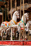 Chevaux blancs caracolants sur le carrousel Image stock