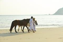 Chevaux de marche d'un couple sur la plage Photographie stock
