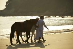 Chevaux de marche d'un couple sur la plage Photo stock