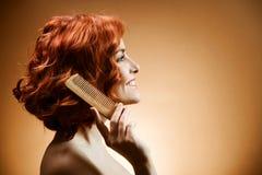 Cheveu bouclé et peigne Photographie stock
