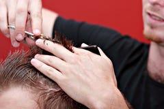 Cheveu de découpage de coiffeur sur le jeune homme Photo libre de droits