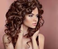Cheveu ondulé Belle fille avec le renivellement Coiffure bouclée Brunette images stock