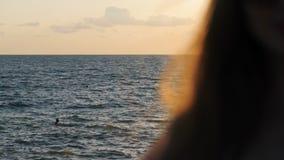 Cheveu oscillant Fille sur la mer au coucher du soleil banque de vidéos