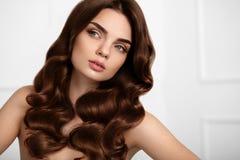 Cheveu sain Belle femme avec la longue coiffure onduleuse enroulements photos libres de droits