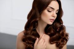 Cheveu sain Belle femme avec la longue coiffure onduleuse enroulements images stock