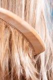 Cheveux bruns droits avec le plan rapproché en bois de peigne photo stock