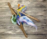 Cheveux colorés et vieux plan rapproché d'axe sur le fond en bois Outils pour le tricotage de la laine Image stock