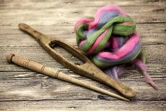 Cheveux colorés et vieux plan rapproché d'axe sur le fond en bois Outils pour le tricotage de la laine Photos stock
