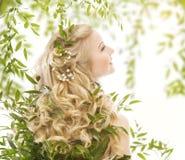 Cheveux dans des feuilles vertes, soin naturel de traitement, femme longtemps bouclée Images stock