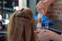 Cheveux de bordage de styliste pour la jeune femme Soin de fille au sujet de sa coiffure Pour faire des boucles photo stock