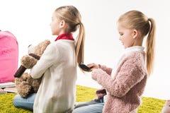 cheveux de brossage d'enfant heureux de soeur tout en se reposant sur le plancher Images libres de droits