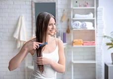 Cheveux de brossage de jeune femme après application du masque photos stock