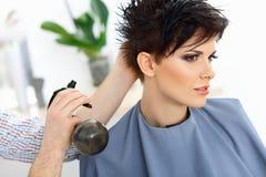 Cheveux de Brown. Le coiffeur faisant la coiffure dans le salon de coiffure. photos libres de droits