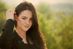 Cheveux de brune de contact de femme longs sur le paysage naturel photos stock