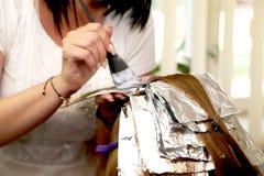 Cheveux de coloration de coiffeur dans le studio photo stock