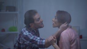 Cheveux de cri et de saisie d'homme fâché d'épouses, assaut dans la famille, temps pluvieux banque de vidéos