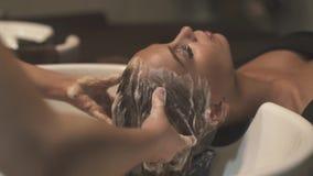 Cheveux de lavage et massage principal dans le salon de beauté avant coupe de cheveux femelle Cheveux de lavage de styliste en co clips vidéos