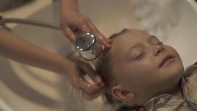 Cheveux de lavage de styliste en coiffure d'enfants avec le shampooing à peu de garçon dans le salon de coiffeur Fermez la tête d banque de vidéos