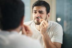 Cheveux de nez beaux de règlage d'homme dans la salle de bains Photos stock