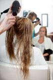 Cheveux de séchage avec le dessiccateur de coup photos stock