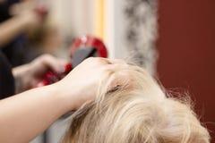 Cheveux de séchage de coiffeur avec le dessiccateur de main photos libres de droits