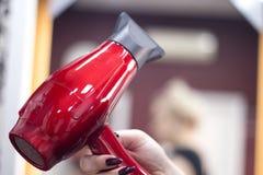 Cheveux de séchage de coiffeur avec le dessiccateur de main photo stock